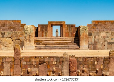 """Tiwanaku, La Paz / Bolivia - September 12 2016: The Famous """"Puerta del Sol"""" (Sun Gate), an Archaeological Monument of the Tiwanaku Culture Surrounded by Ruins and a Monolith in the Background"""