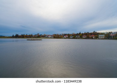 Tjornin pond great place popular destination for families Reykjavik. Water surface pond scandinavian city. Pond or lake nature environment destination. Pond surrounded numerous coloured old houses.