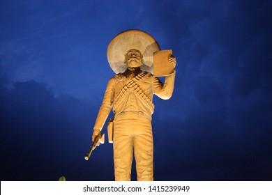 Tlaltizapan, Morelos / Mexico - May 5, 2018: Statue at night of Mexican revolutionary leader Emiliano Zapata holding The Plan of Ayala (Spanish: Plan de Ayala) during the Mexican Revolution.
