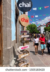 Tlaquepaque, Jalisco, Mexico - September 15 2019: Chai cafeteria and restaurant. Mexican flags. Male and female couple walking by. Wooden sign reads bazar, arte insurgente, Juana Bautista