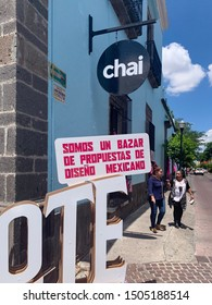 "Tlaquepaque, Jalisco, Mexico - September 15 2019: Large wood sign for Mitote, reading ""we are a mexican design bazar"". Two females chat on the sidewalk by Chai Restaurant cafe"