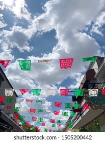 Tlaquepaque, Jalisco, Mexico - September 15 2019: Red, white and green flag ornaments under a beautiful blue sky with pristine white clouds