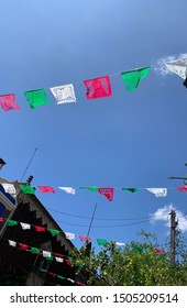 Tlaquepaque, Jalisco, Mexico - September 15 2019: Red, white and green flag ornaments under a beautiful blue sky