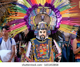 Tlaxcala, Mexico, February 20, 2020.  People in Huehue costumes walking the street in the opening parade of the 2020 under watchful eyes of crowd. Girls wear dresses, man outfit with masks, feathers
