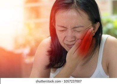 TMD and TMJ concept: Temporomandibular Joint and Muscle Disorder. Asia woman hand on cheek face as suffering from facial pain, mumps  or toothache