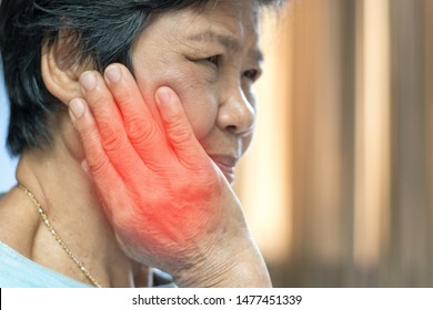 TMD and TMJ concept: Temporomandibular Joint and Muscle Disorder. Old Asia woman hand on cheek face as suffering from facial pain, mumps or toothache