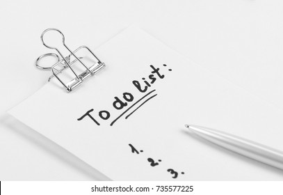 """to do list"" is written on notepad with pen on office table,  on white  background. Top View."