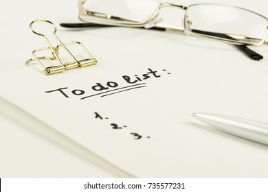 """to do list"" is written on notepad with pen on office table, glasses on white  background."