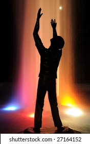 """""""To Worship God"""" -- A silhouetted statue with a lighted water fountain in the background."""