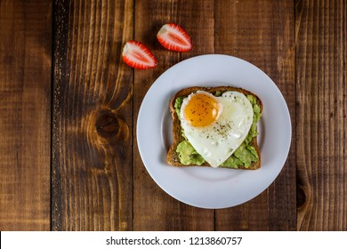 Toast with avocado and egg in heart shape and strawberries