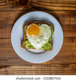 Toast with avocado and egg with heart shape  on white plate