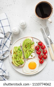Toast with avocado, fried egg, tomatoes and cup of black coffee americano on bright concrete background. Top view and copy space for text