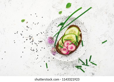 Toast avocado puree, cucumber, onion, onion flowers, radish and daikon on slices of dark bread on a light background with sesame seeds. Top view, copy space