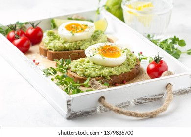 Toast with avocado puree and soft boiled egg on white tray, liquid yolk, delicious breakfast, light sandwich. Healthy food