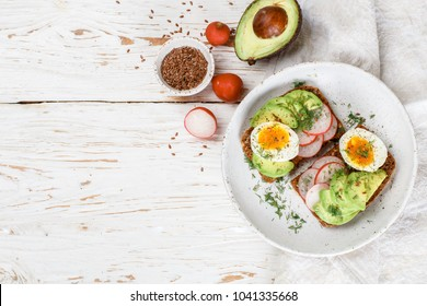 Toast with avocado, radish, egg and flax seeds.  Delicious healthy Breakfast on a white wooden table. Selective focus and copy space