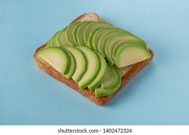 Toast with avocado slices on blue background. Tasty and eye-pleasing snack. Vegan food, light and easy breakfast idea.