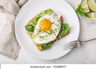 toast with avocado, spinach and fried egg, top view