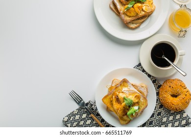 Toast with banana and mint, cup of coffee and bun with towel on white background top view with empty space. Elvis sandwich