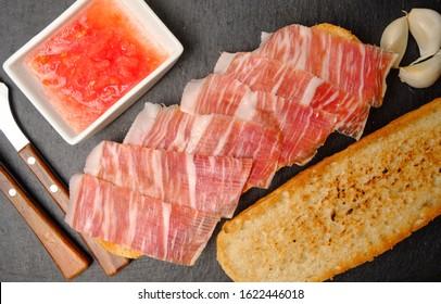Toast of bread with acorn-fed Iberian ham on stone slate