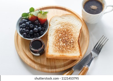 toast bread with blueberry and strawberry served with black coffee and blueberry jam.