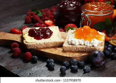 Toast bread with homemade strawberry jam and apricot marmalade on rustic table served with butter for breakfast or brunch.