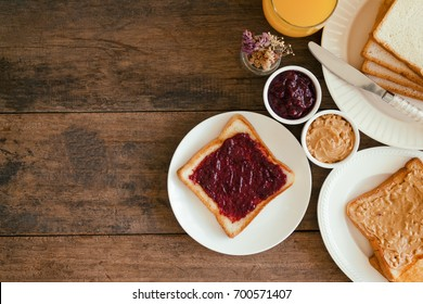Toast bread with homemade strawberry jam and peanut butter on rustic wood table served with fresh orange juice in top view flat lay with copy space for breakfast or brunch.