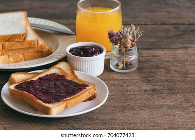 Toast bread with homemade strawberry jam on rustic wood table served with fresh orange juice in side view with copy space for breakfast or brunch.