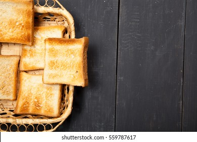 Toast the bread on a black wooden background