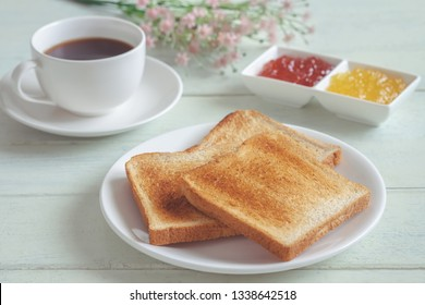 Toast bread on plate with jam and coffee cup