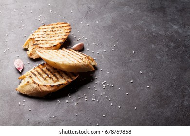 Toast bread with salt and garlic on stone table. View with copy space