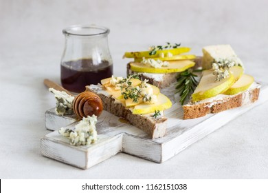 Toast or bruschetta with ricotta or cream cheese, pear, honey and blue cheese on white wooden cutting board. Delicious breakfast or snack on a light background.