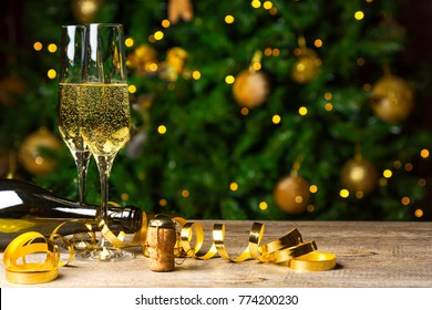 Toast Champagne, flutes on wooden floor, Christmas tree background