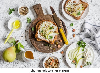 Toast with cheese, pear, honey and nuts. Delicious breakfast or snack on a light background, top view