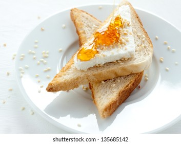 Toast with cottage cheese, sesame and honey on white plate - healthy breakfast composition