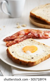 toast with egg in a hole served with bacon and drink for breakfast