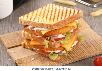toast fried chicken sandwich, hummer sandwich, clubhouse sandwich on wood background with raw vegetables and fries