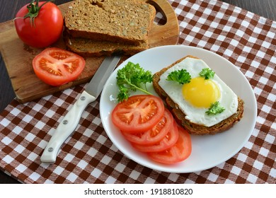 toast with fried egg and tomatoes on the wholegrain bread with parsley