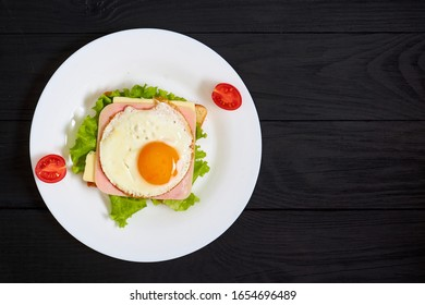Toast with ham, egg and tomato on a plate on a black background.