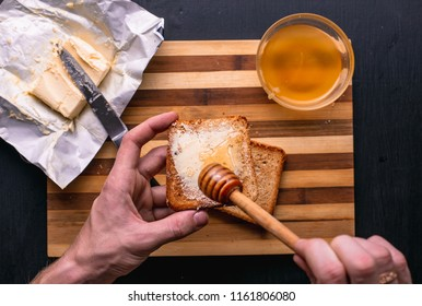 Toast with honey on wooden plate