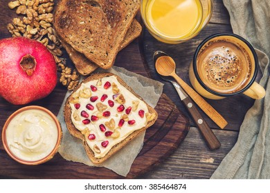 Toast with hummus, wallnuts and pomegranate on rustic wooden background. Healthy breakfast.