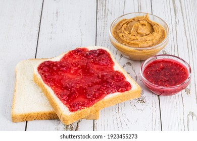 toast with jam and peanut butter on a light wooden background.