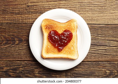 Toast with jam in shape of hearts on wooden background. Top view