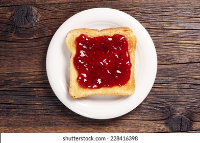 Toast with jam in white plate on dark wooden table. Top view