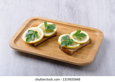 toast with lemon and parsley on a wooden plate