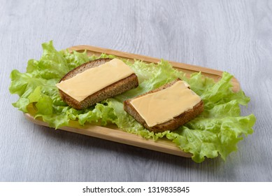 toast with lettuce leaf and cheese on a wooden plate