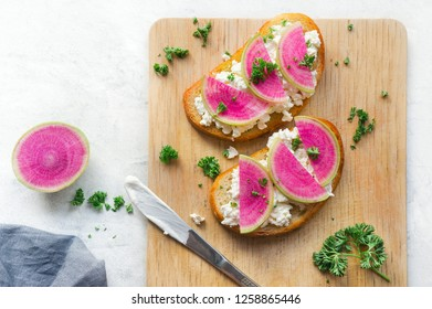 Toast made from sliced watermelon radish (chinese daikon), cottage and parsley. Top view.