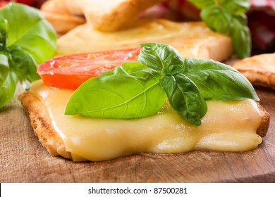toast with melted cheese, tomato and basil
