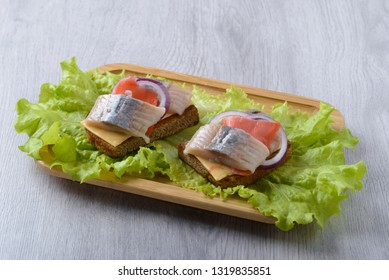 toast on a leaf of salad with herring, cheese and ginger on a wooden plate
