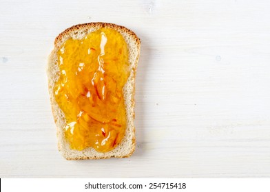 Toast with orange marmalade on a white table top view
