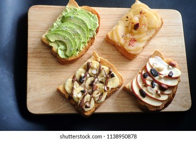 Toast party on wooden tray – avocado, salt + pepper avocado / Apple  peanut butter almonds  raisins honey/ banana ,dark chocolate /peach ,cinnamon , cream cheese, rose Isolated on wooden background.
